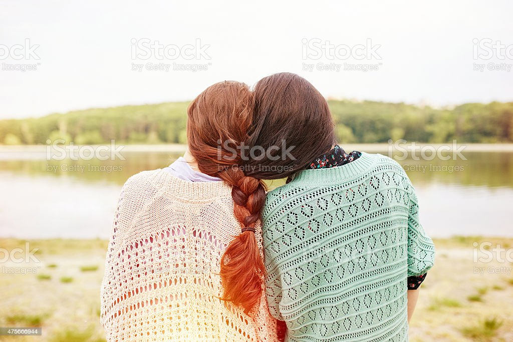 Two sisters with interwoven hairs stock photo