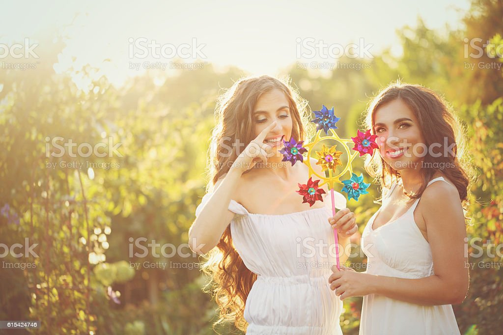 Two sisters with windmill stock photo