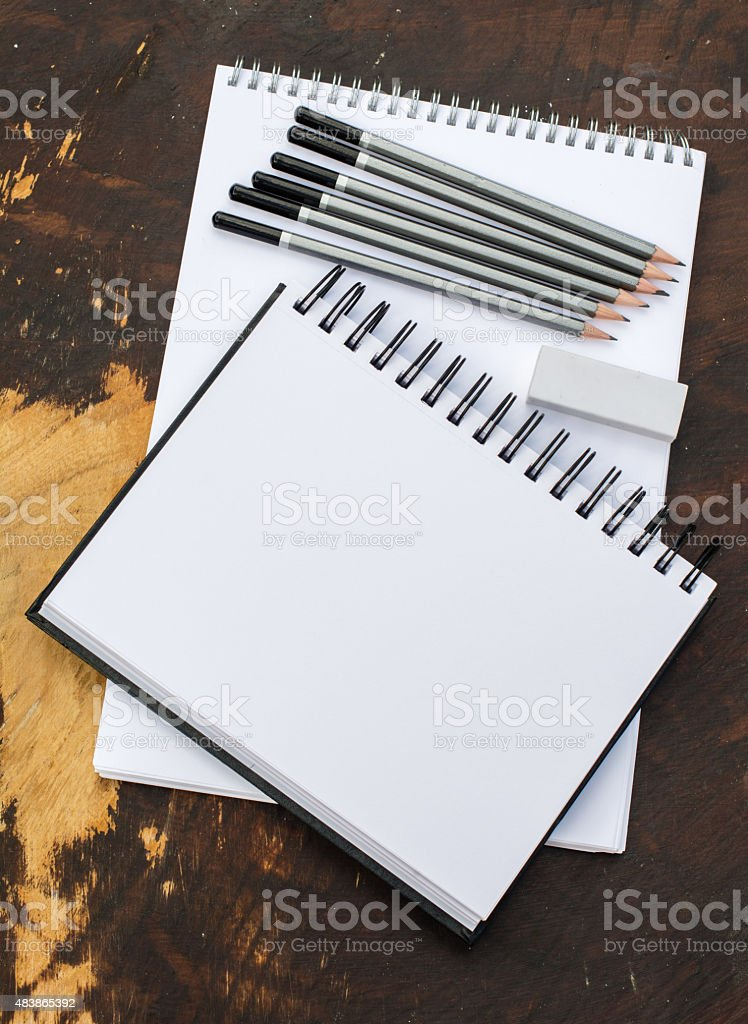 Two sketchpads, pencils, eraser and the laptop on dark table stock photo