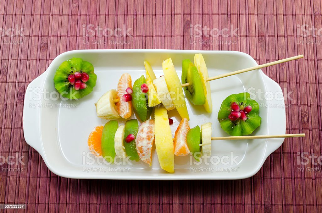 Two skewers full with colourful fruit on a table royalty-free stock photo
