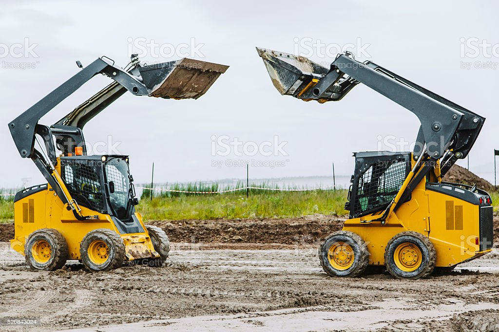 two skid steers moving dirty outdoors stock photo