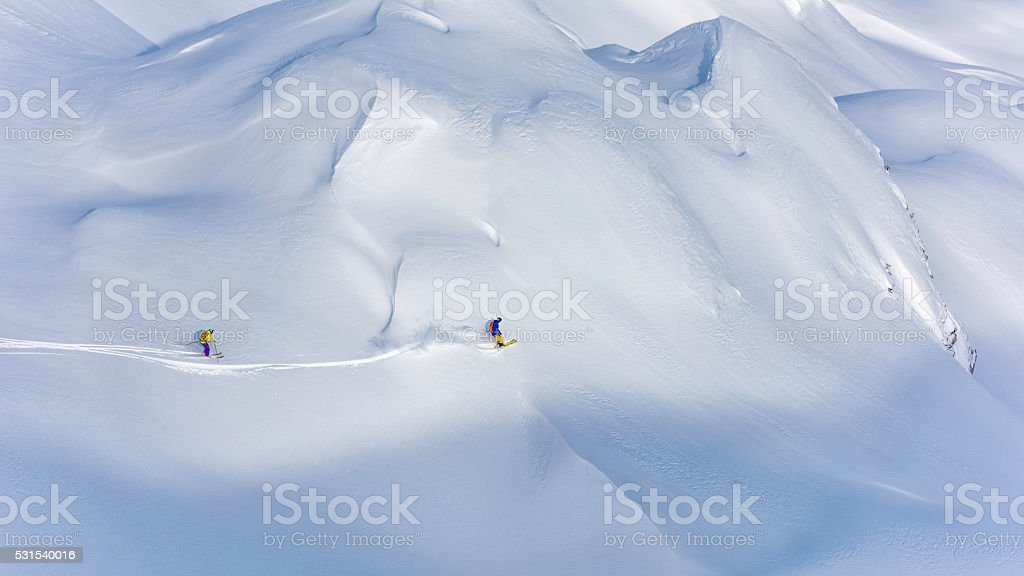 Two off-piste skiers skiing on a snow covered hill, viewed from afar.