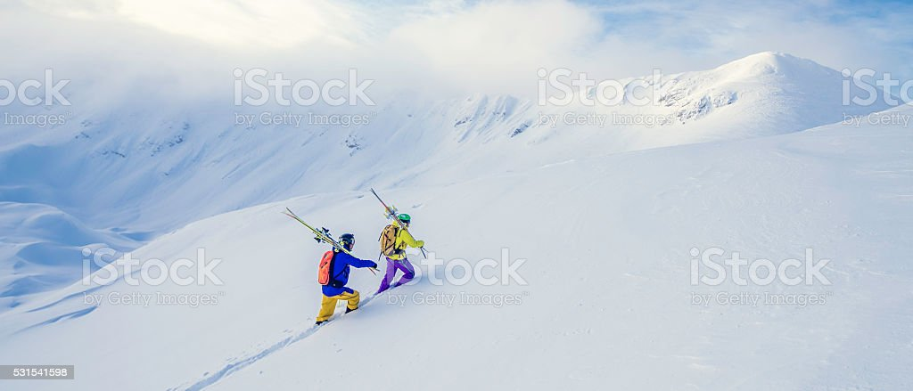 Two skiers climbing up a snow-covered hill stock photo