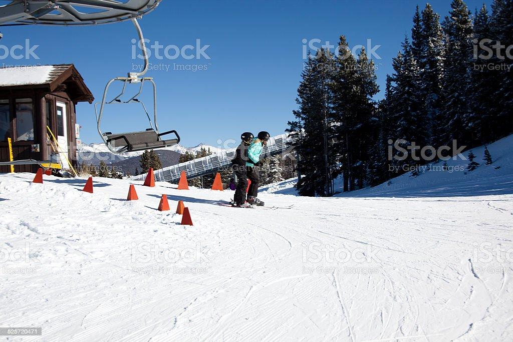 Two skiers exit ski lift. Top of mountain. Winter. Colorado. stock photo