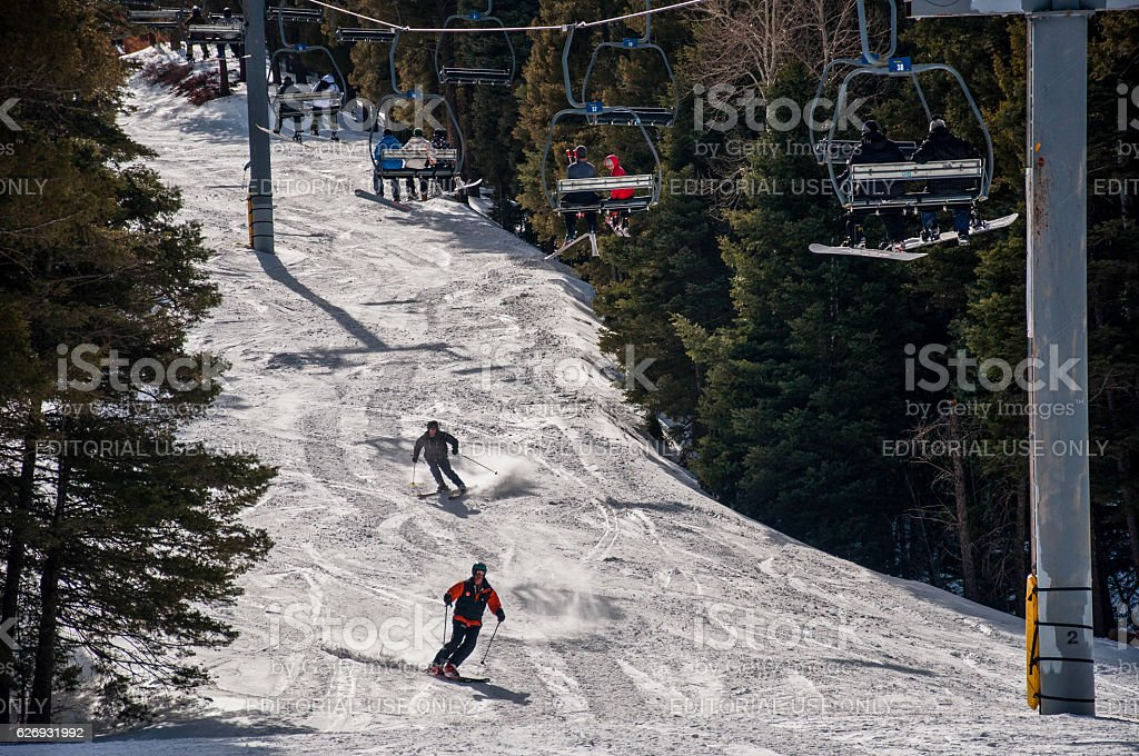 Two Skiers Race down Slope More Ride Ski Lift stock photo