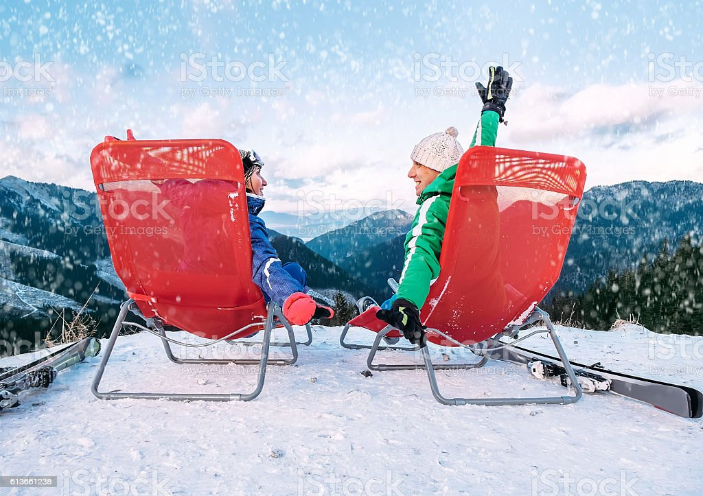 Two skiers relax in chiars on the mountain top stock photo