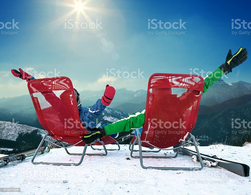 Two skiers sitting in chaise-longues on the top of mountain stock photo