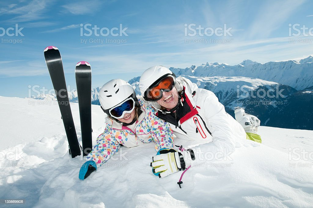 Two skiers taking a break and playing in the snow royalty-free stock photo