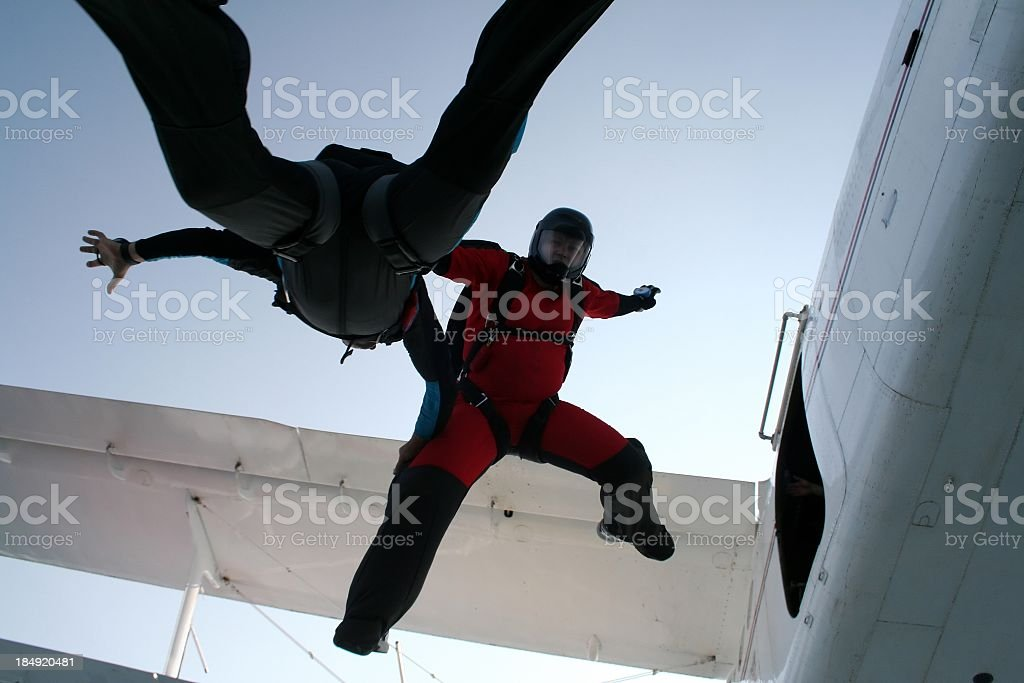 Two skydivers exiting a biplane royalty-free stock photo