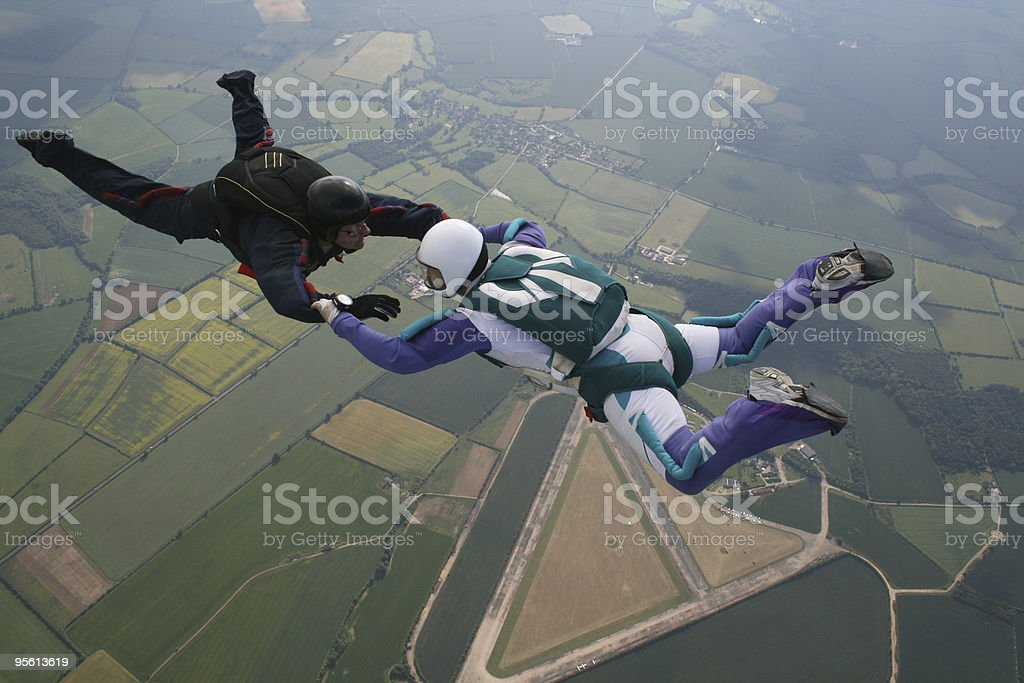 Two skydivers holding hands in midair royalty-free stock photo