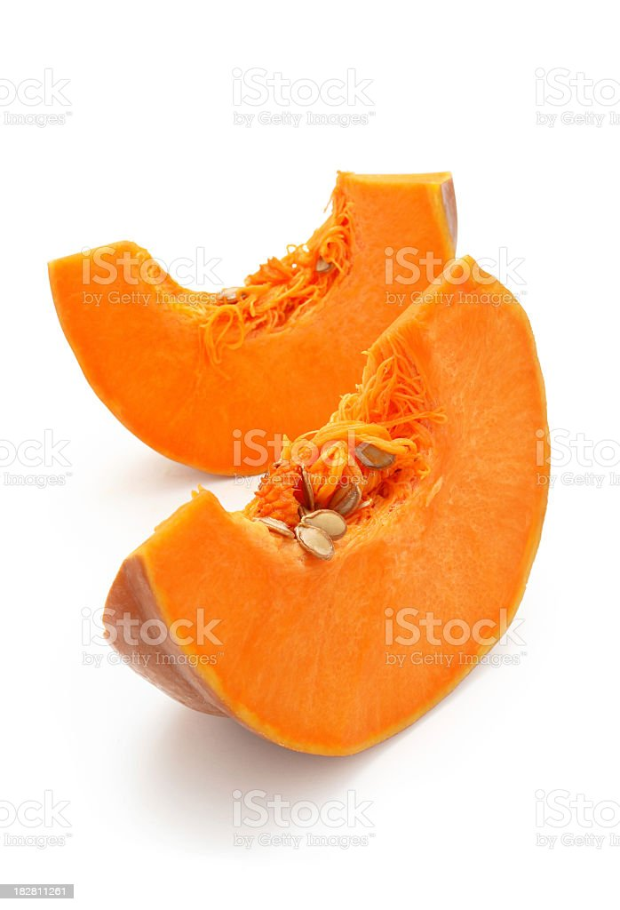 Two slices of pumpkin with the seeds still in stock photo