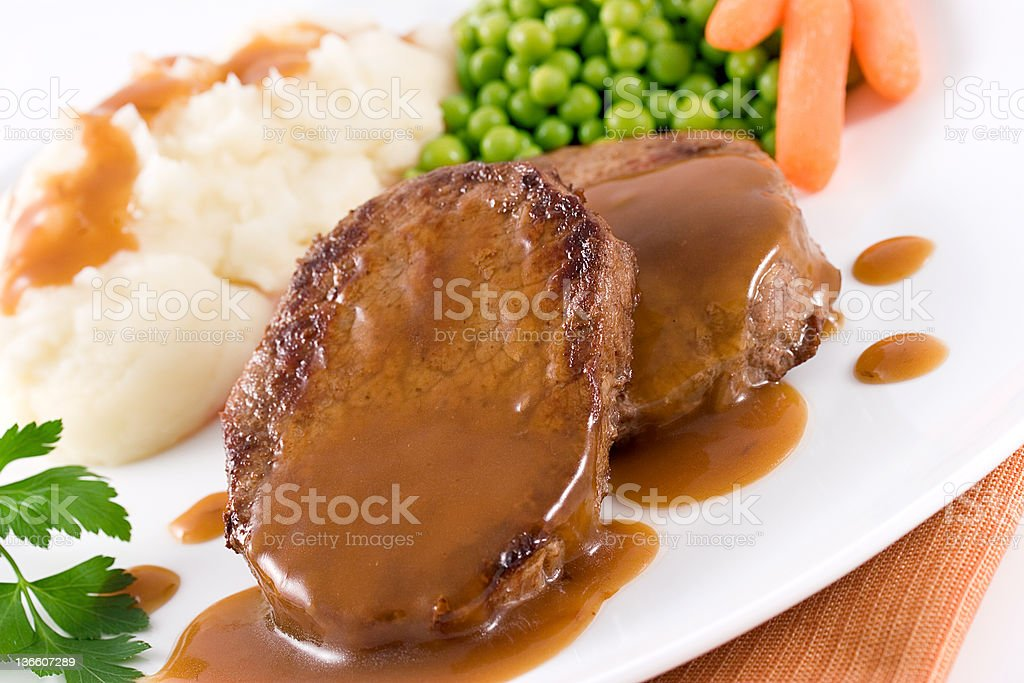 Two slices of roast beef with brown gravy royalty-free stock photo