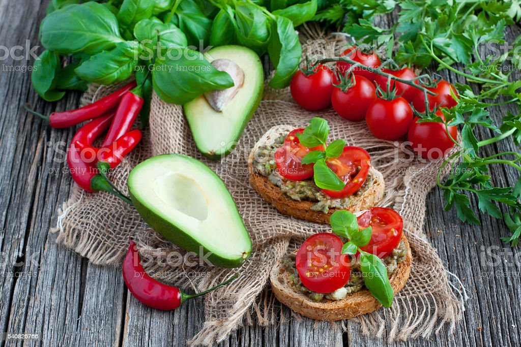 Two slices of rye bread with  avocado on  wooden  background stock photo
