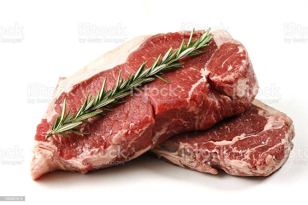 Two slices of thick cut steaks with a green leaf on top royalty-free stock photo