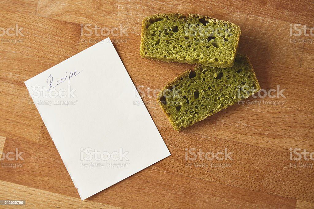 Two slices spinach bread isolated with recipe on wooden table stock photo