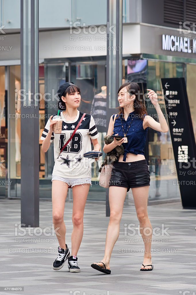 Two slim, fashionable girls at Beijing The Village shopping area stock photo