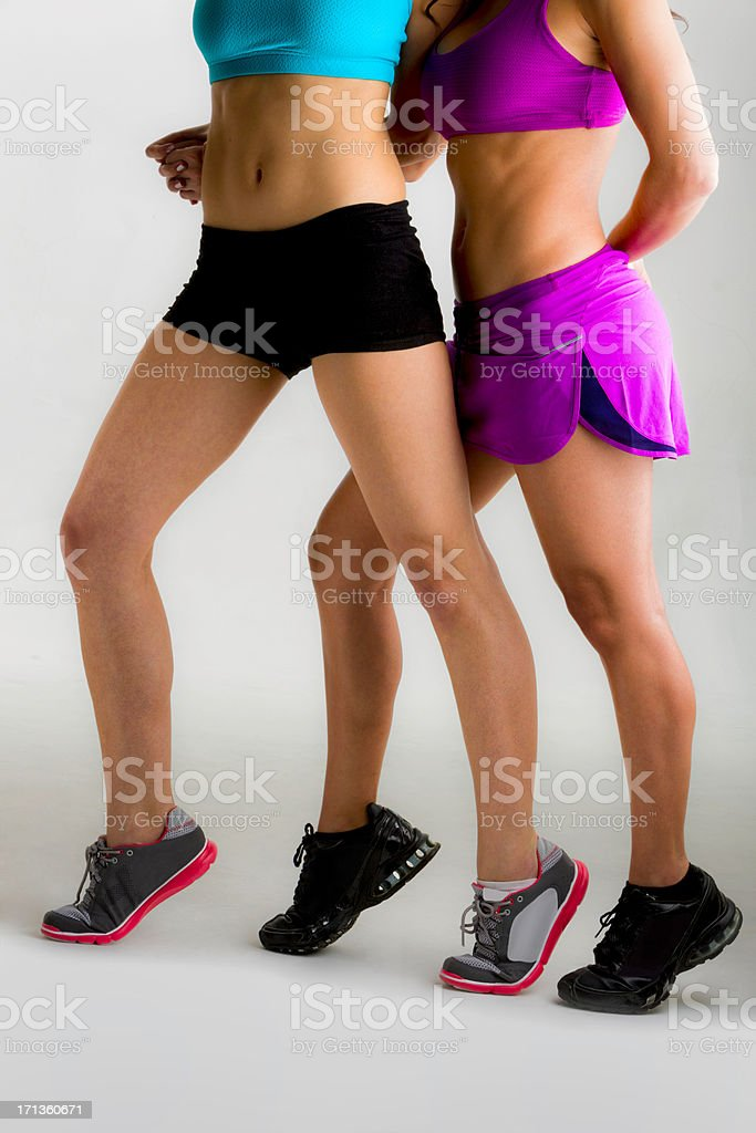 Two slim young woman showing leg muscles after pilates workout stock photo