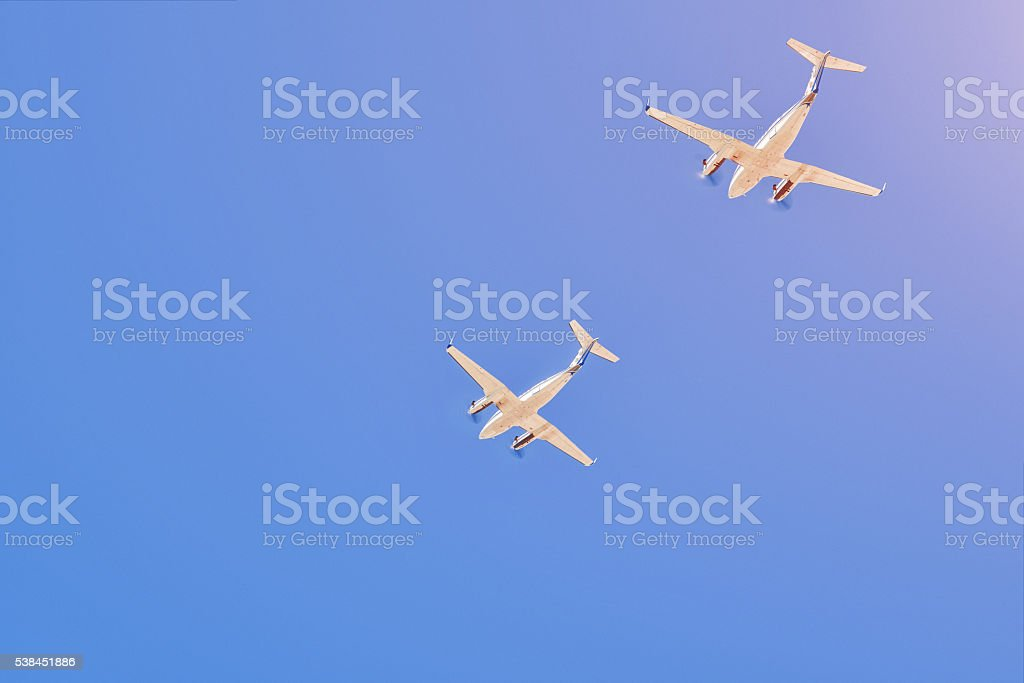 Two small aircrafts flying in a blue sky stock photo