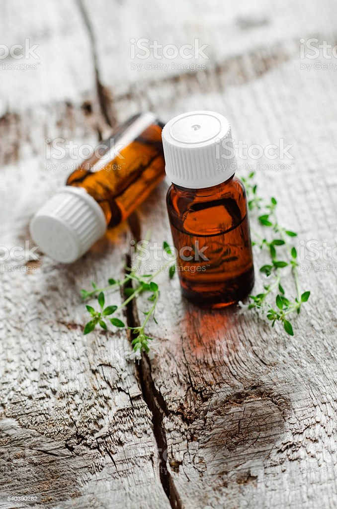 Two small bottles of essential thyme oil stock photo