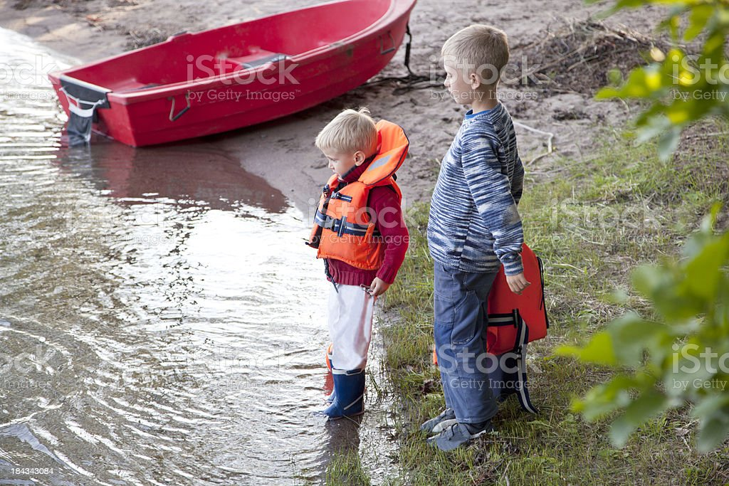 Two small boys and a red boat on the beach. royalty-free stock photo