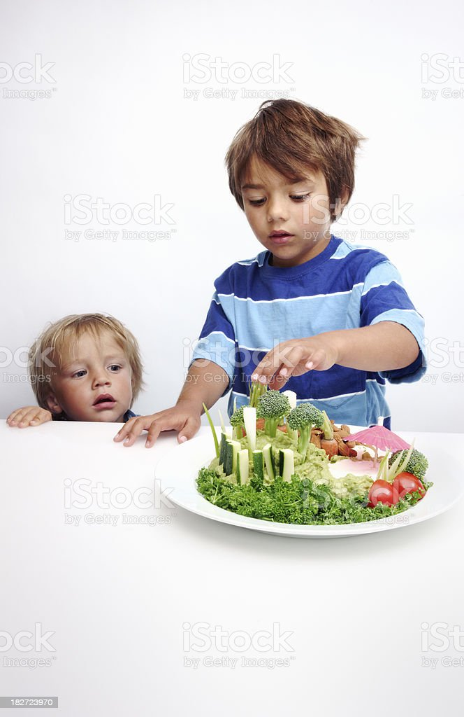 Two small boys enjoying a vegetable plate royalty-free stock photo