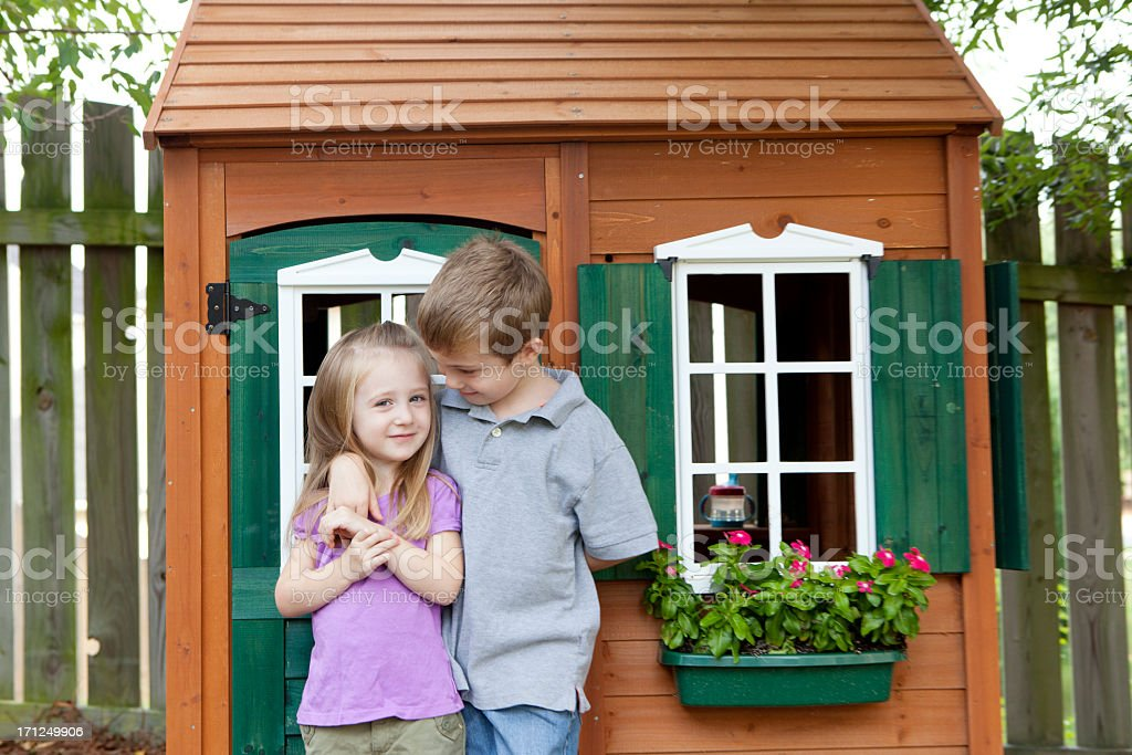Two small children standing in front of a wooden playhouse stock photo