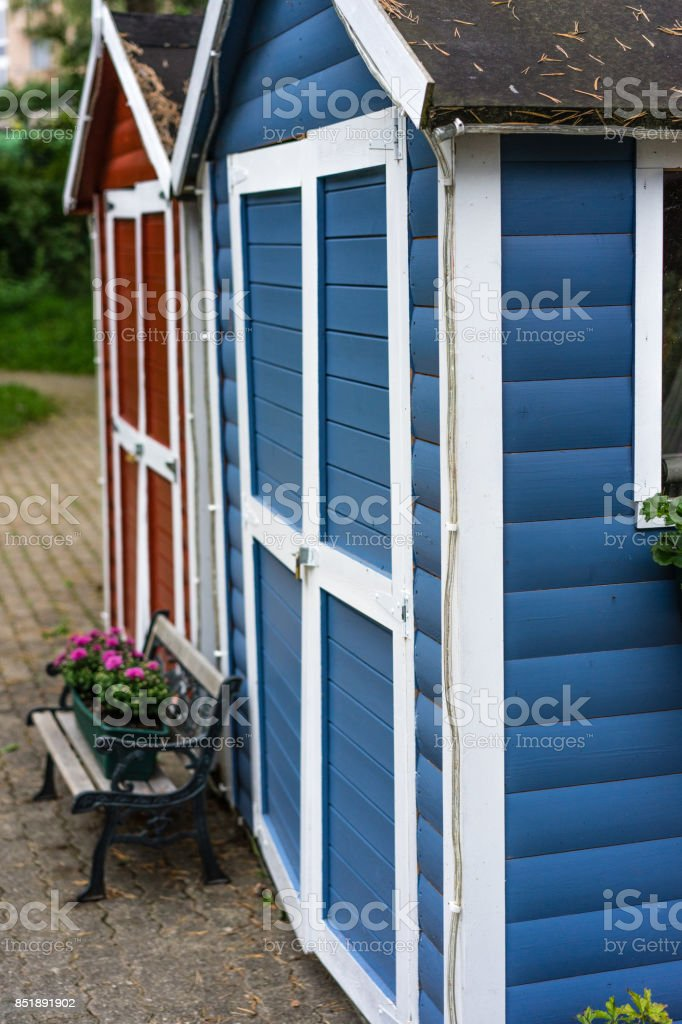 two small red and blue house with wood boards and flower bouquet scandinavian style stock photo