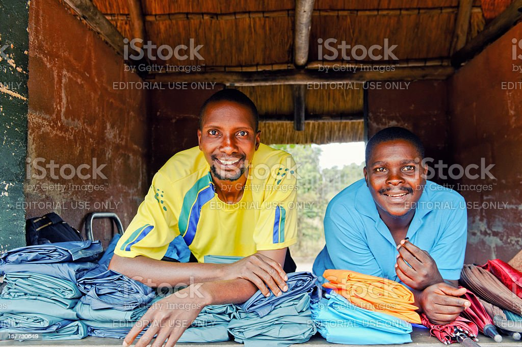 Two smiling African vendors renting rain clothing in shop,Zimbabwe stock photo