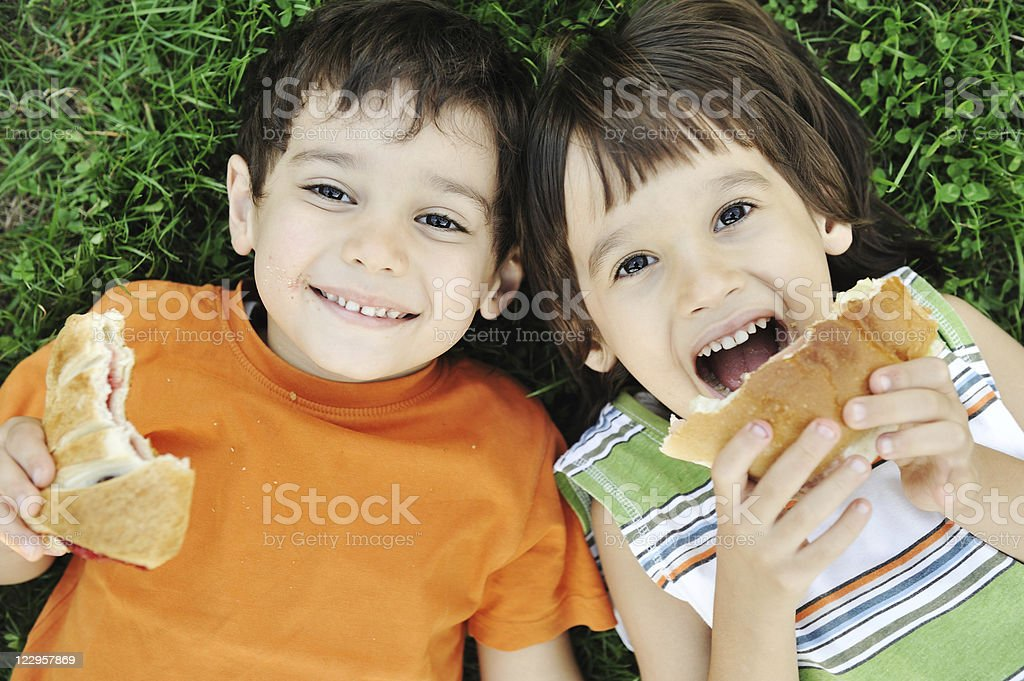 Two smiling boys with snacks on green grass stock photo