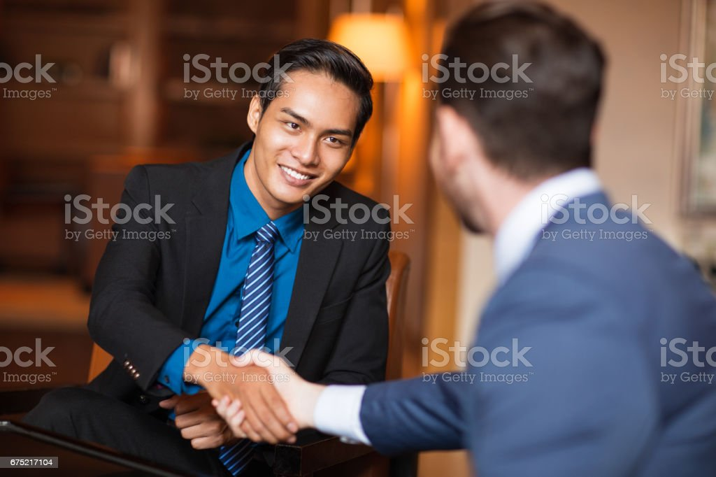 Two Smiling Business Partners Shaking Hands stock photo