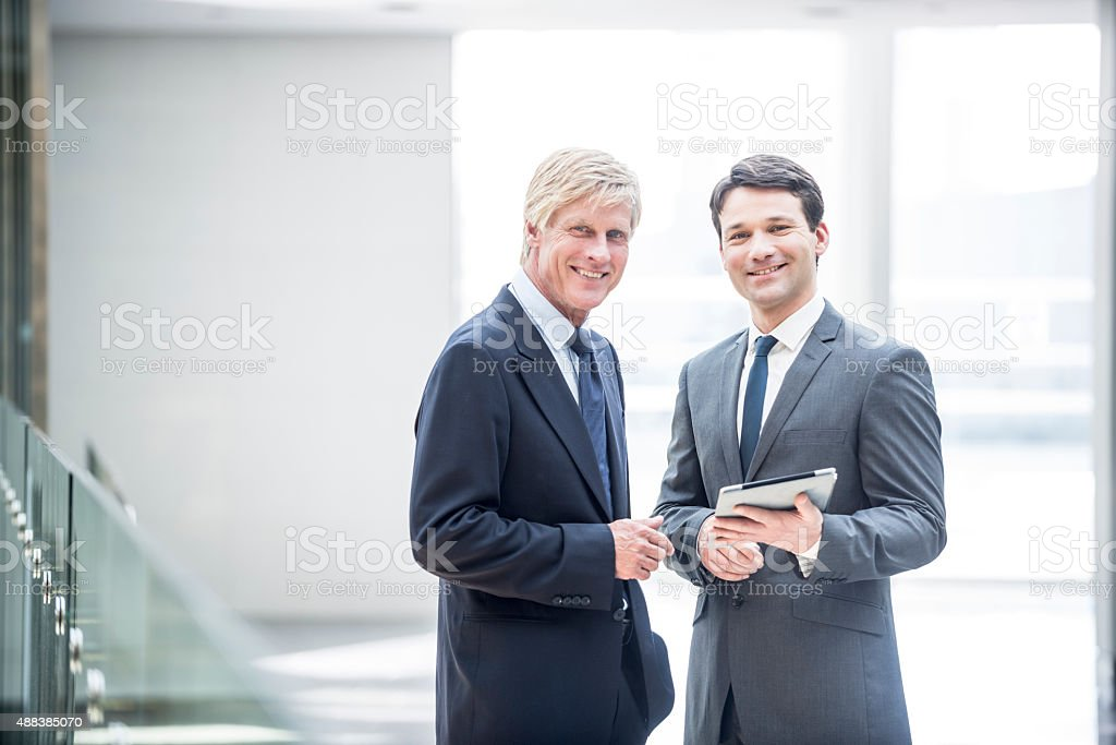 Two smiling businessman with digital tablet stock photo