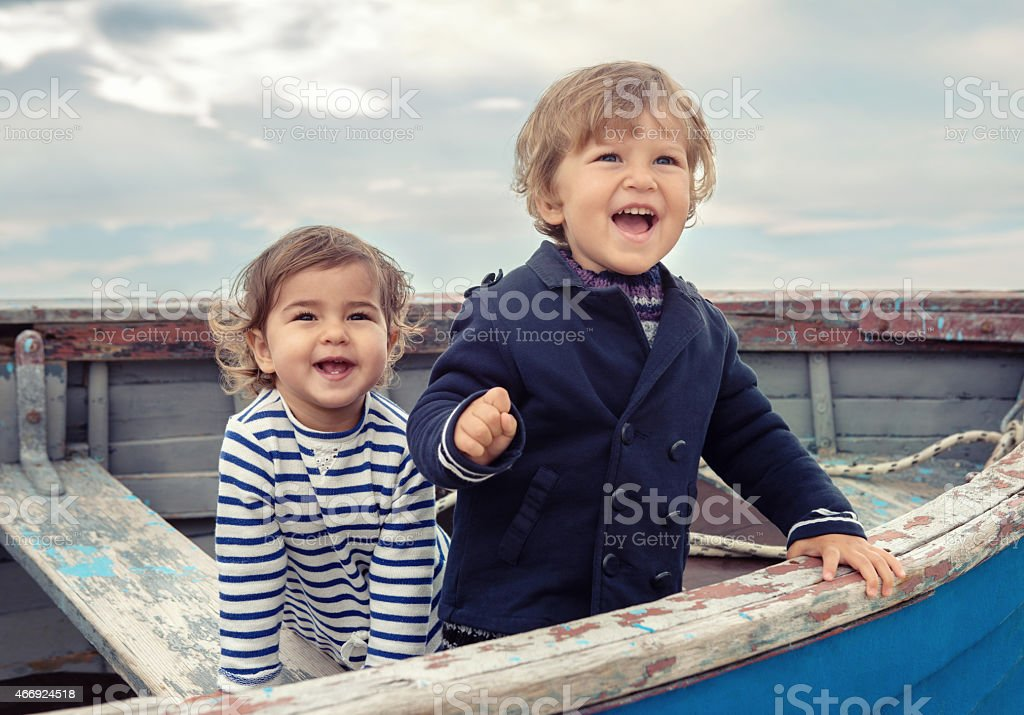 Two smiling children playing in a worn rowboat stock photo