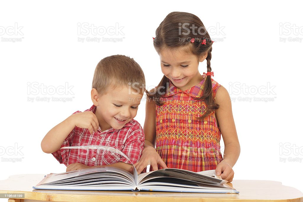 Two smiling children reading book on the desk royalty-free stock photo