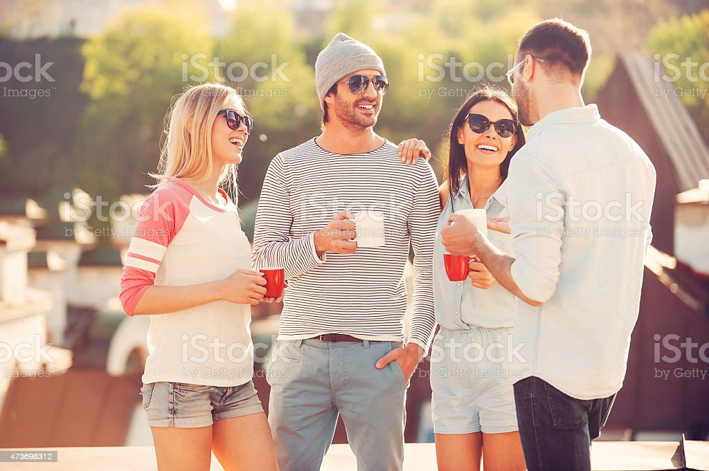 Two smiling couples standing while on their coffee break stock photo