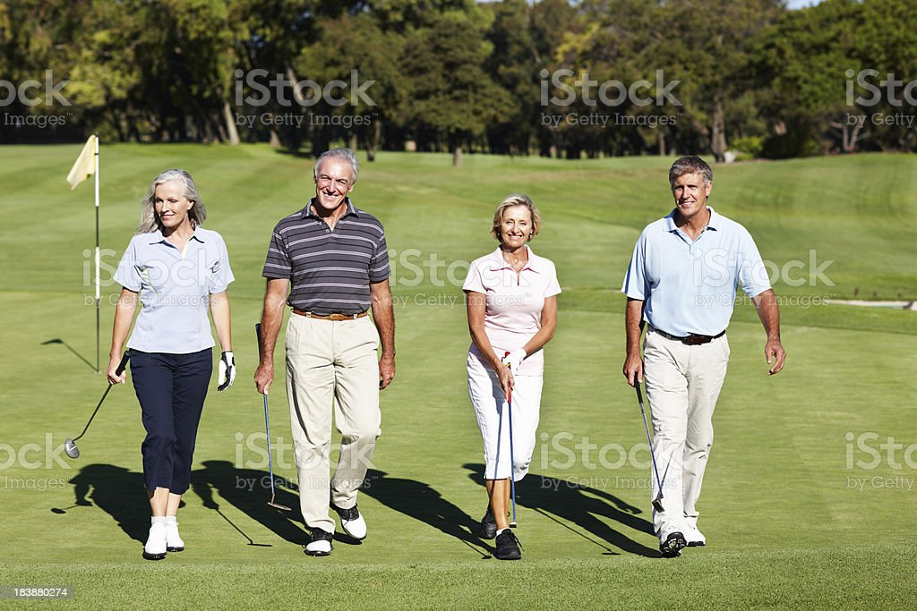 Two smiling couples walking on a golf course royalty-free stock photo