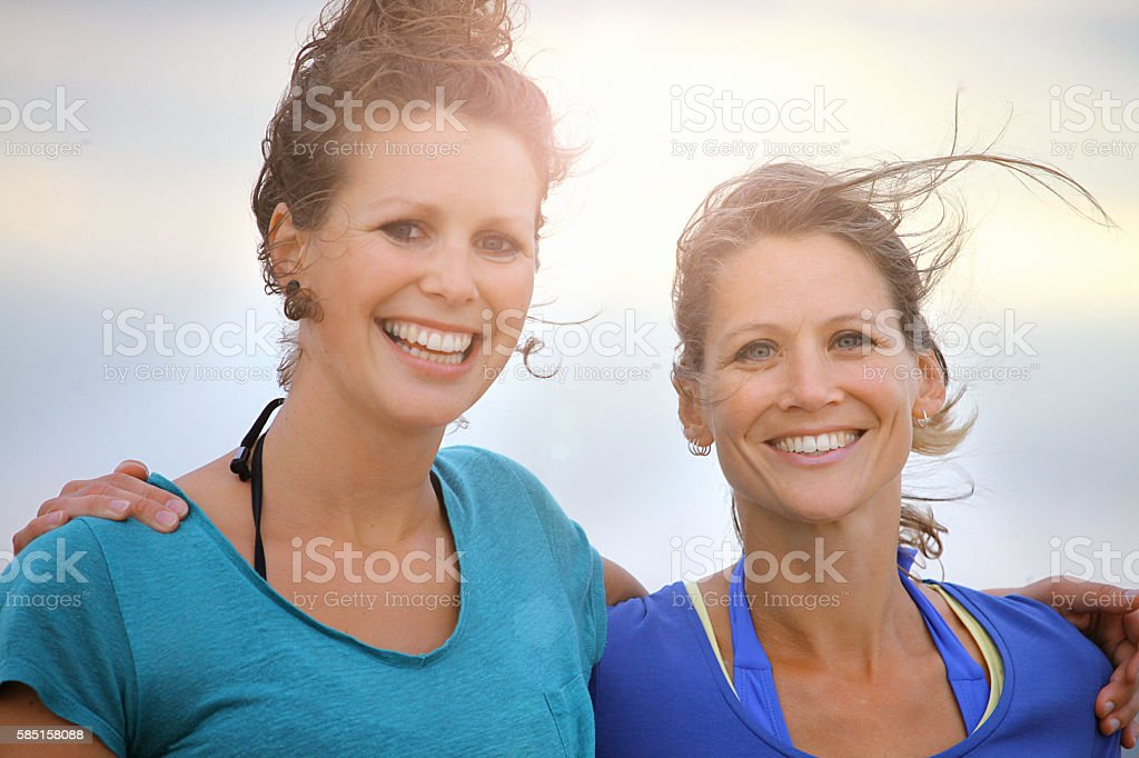 Two smiling female friends posing for a summer photo stock photo