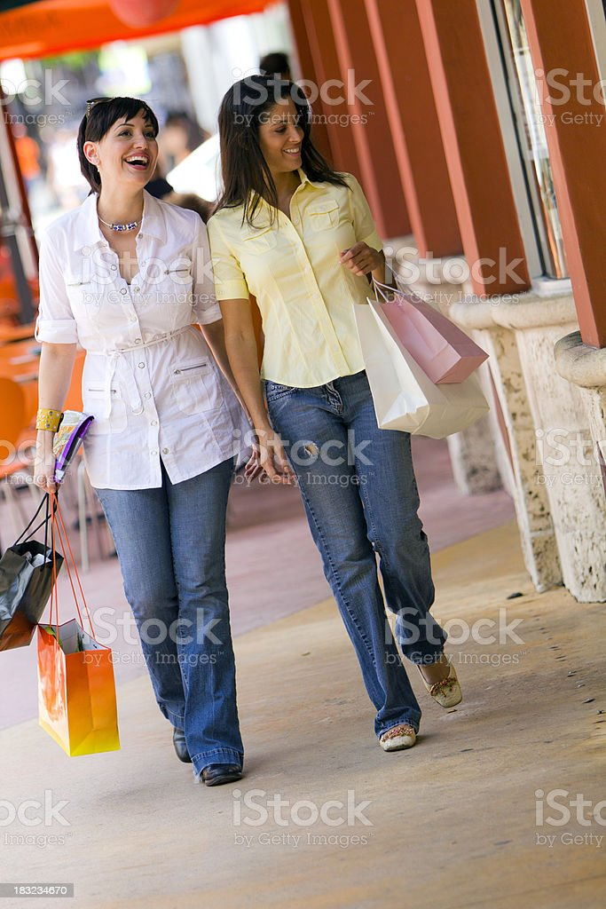 Two smiling females walking holding bags while shopping royalty-free stock photo