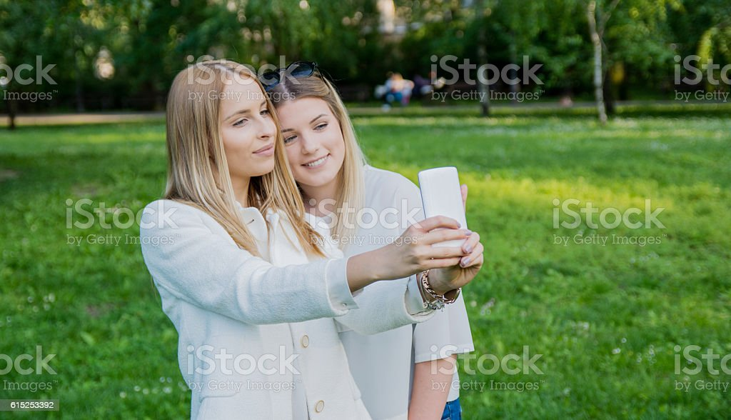 Two smiling girls taking a selfie in the park stock photo
