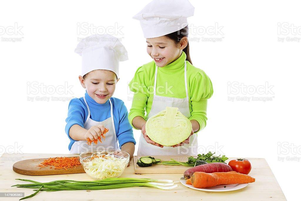 Two smiling kids preparing salad stock photo