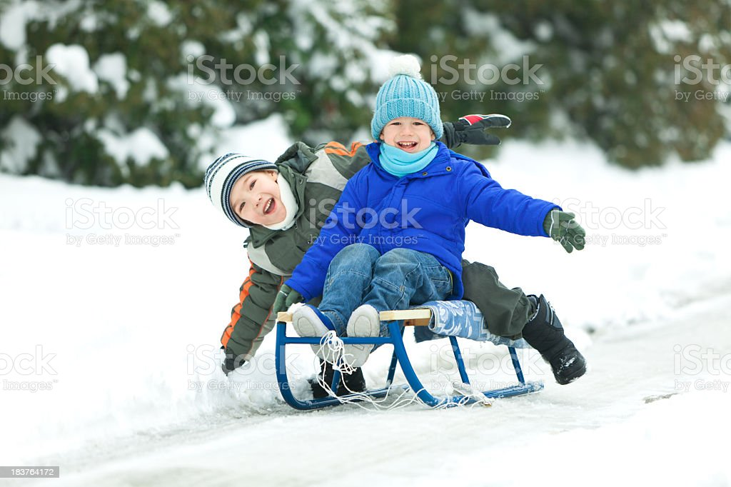 Two smiling little boys sledding in snow royalty-free stock photo