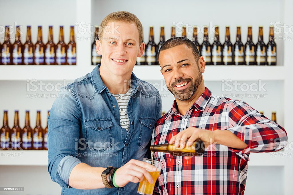 Two smiling men pouring beer stock photo