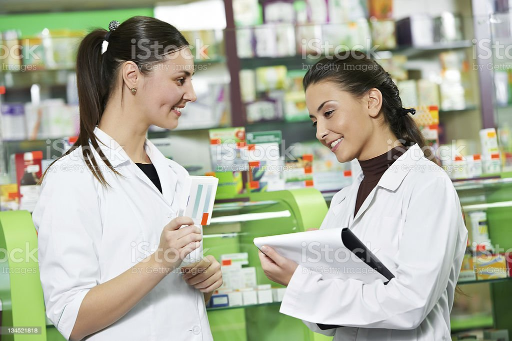 Two smiling pharmacists working in the drugstore royalty-free stock photo