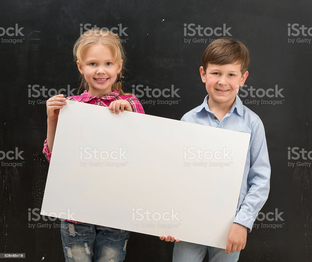 two smiling schoolchildren with blank sheet of paper stock photo
