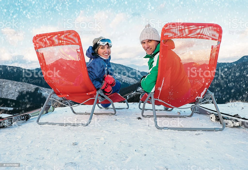 Two smiling skiers sit in chaise-longue on the mountain top stock photo