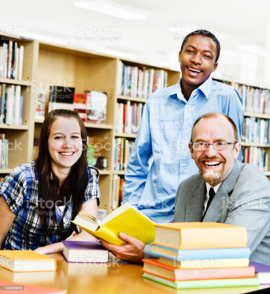 Two smiling students and their professor in campus library royalty-free stock photo
