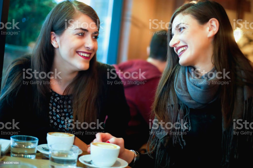 Two smiling students having a cup of coffee in cafe stock photo