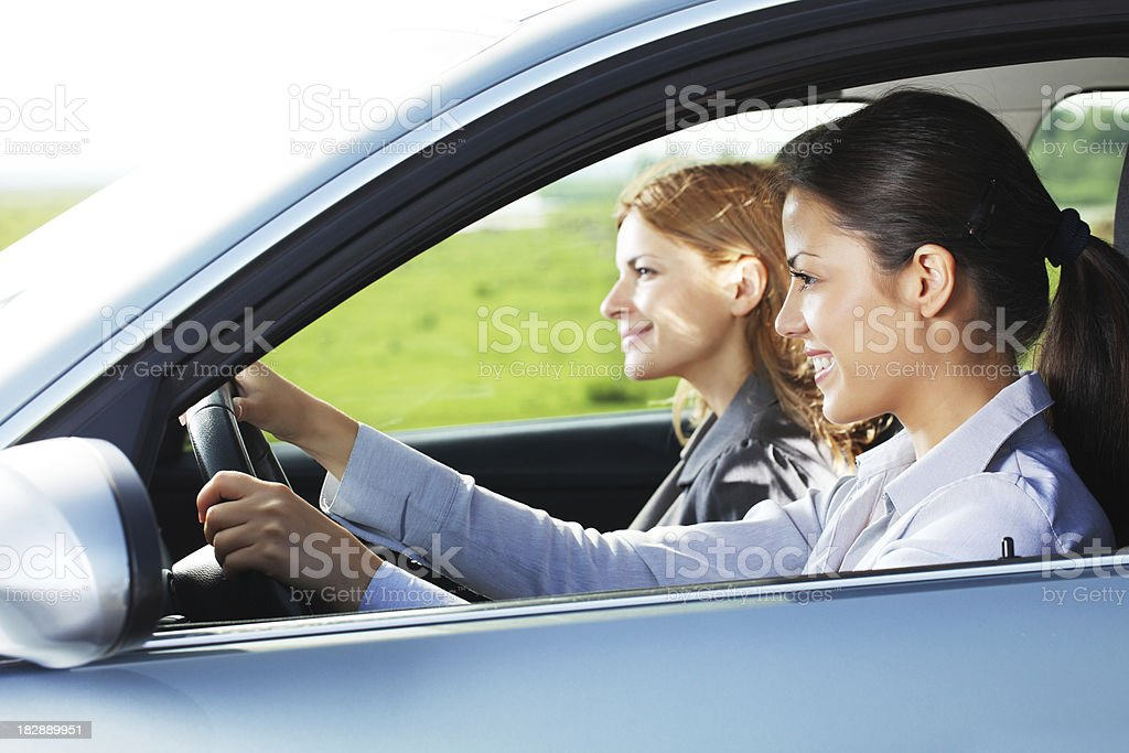 Two smiling women drive a car. royalty-free stock photo