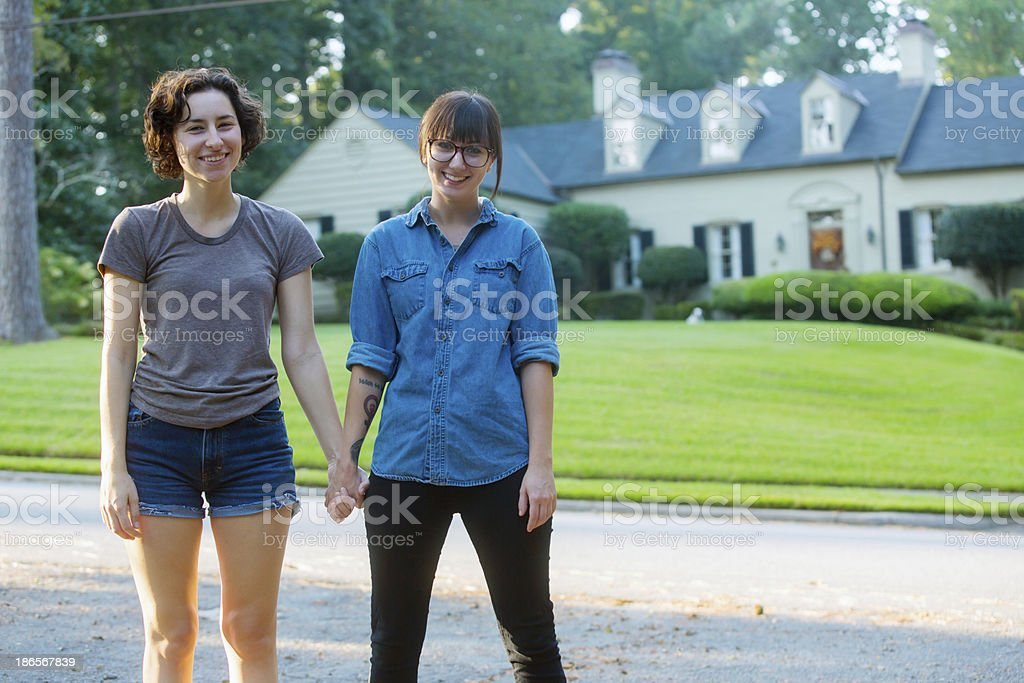 Two smiling women holding hands with house in background royalty-free stock photo