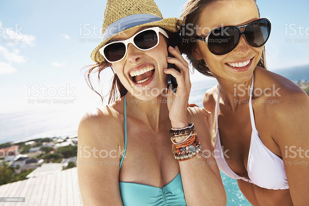 Two smiling women in swimsuits with mobile phone royalty-free stock photo