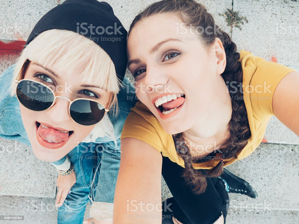 Two smiling women sitting on colorful stairs and having fun stock photo